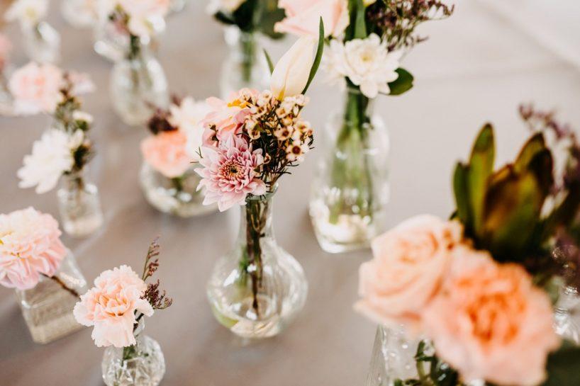 Pastelowe kwiatki w małych szklanych wazonikach na szarym obrusie, What a lovely day Wedding Planner Poznań