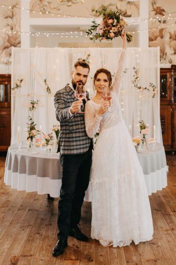 Para Młoda wznosząca toast z różowych kieliszkach, w tle okrągły stół i tiulowa ścianka, What a lovely day Wedding Planner Poznań