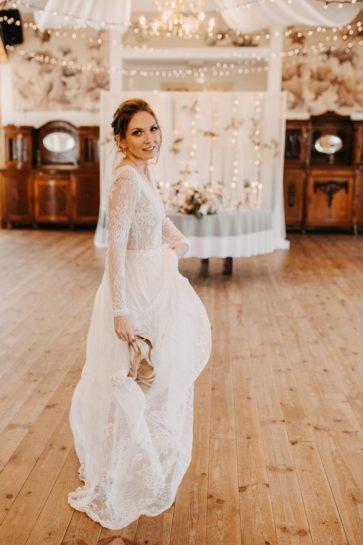 Uciekająca boso Panna Młoda, w tle sala weselna z połyskującymi lampkami, What a lovely day Wedding Planner Poznań