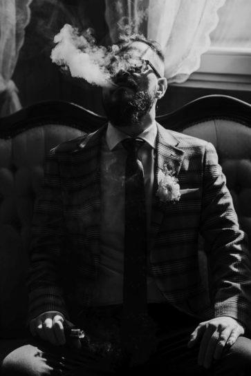 Czarno biały portret Pana Młodego puszczającego kłęby białego dymu, What a lovely day Wedding Planner Poznań