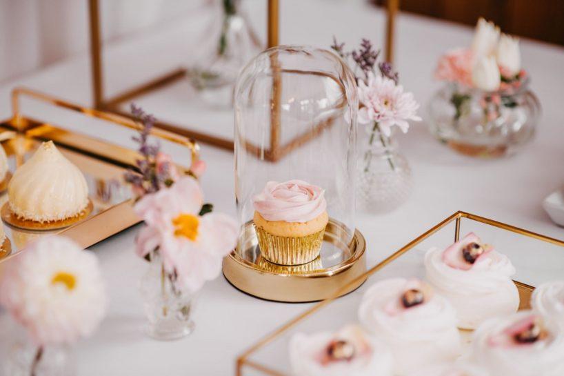 Słodki stół i fokus na różową babeczkę pod złotym kloszem, What a lovely day Wedding Planner Poznań
