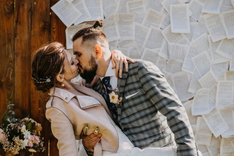 Całująca się Para Młoda, w tle ścianka ślubna z karteczek, What a lovely day Wedding Planner Poznań