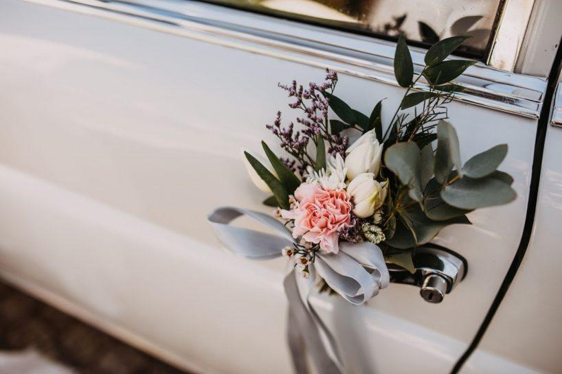 Fokus na kwiatową ozdobę zawieszoną na klamce zabytkowego auta, What a lovely day Wedding Planner Poznań