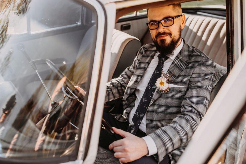 Portret uśmiechniętego Pana Młodego za kierownicą zabytkowego auta, What a lovely day Wedding Planner Poznań