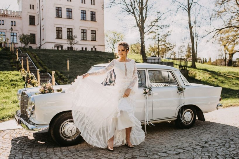 Panna Młoda eksponująca piękną, koronkową suknię ślubną, w tle zabytkowe auto, What a lovely day Wedding Planner Poznań