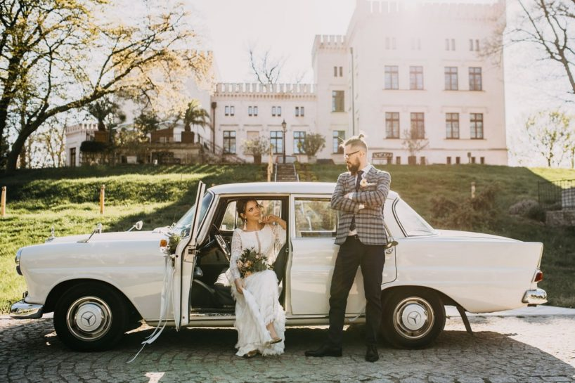 Pan Młody oparty o zabytkowe auto ślubne, Panna Młoda siedząca na miejscu kierowcy, What a lovely day Wedding Planner Poznań