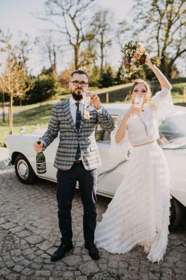 Para Młoda wznosząca toast szampanem, w tle zabytkowe auto, What a lovely day Wedding Planner Poznań