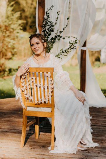 """Uśmiechnięta Panna Młoda w altance ślubnej, siedząca na krześle ozdobionym drewnianą obręczą """"żona"""", What a lovely day Wedding Planner Poznań"""