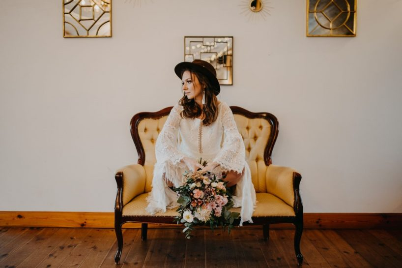 Kucająca Panna Młoda na retro kanapie z dużym, pastelowym bukietem, What a lovely day Wedding Planner Poznań