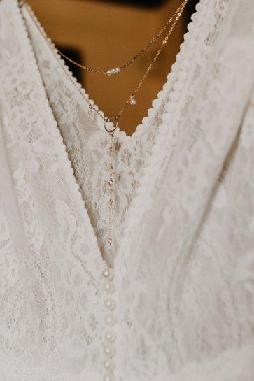 Zbliżenie na koronkową suknię ślubną z ozdobnymi plecami z delikatnego naszyjnika, What a lovely day Wedding Planner Poznań